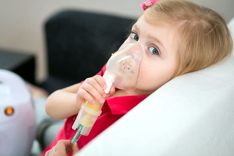 Girl with nebulizer suffering from breathing problems