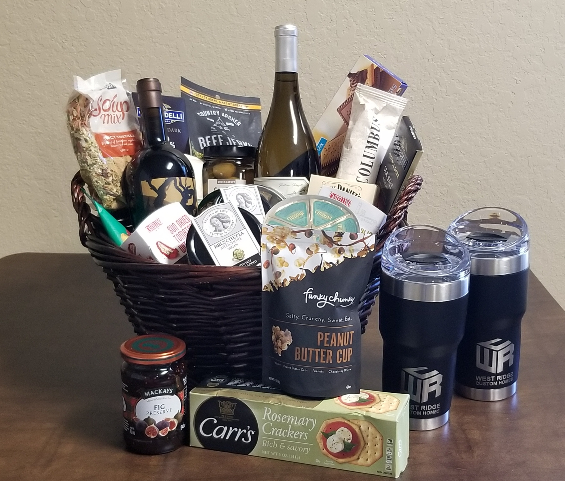 Online Secret Auction: Wines (2), charcuterie and chocolates, Pelican Travel Tumblers (2) w/slide lids presented in a decorative wicker basket